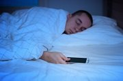 man sleeping in bed with phone